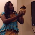 Jamilah is showing us a beautiful gold handbag. Her outfit is what most Ghanaians would wear to a wedding.